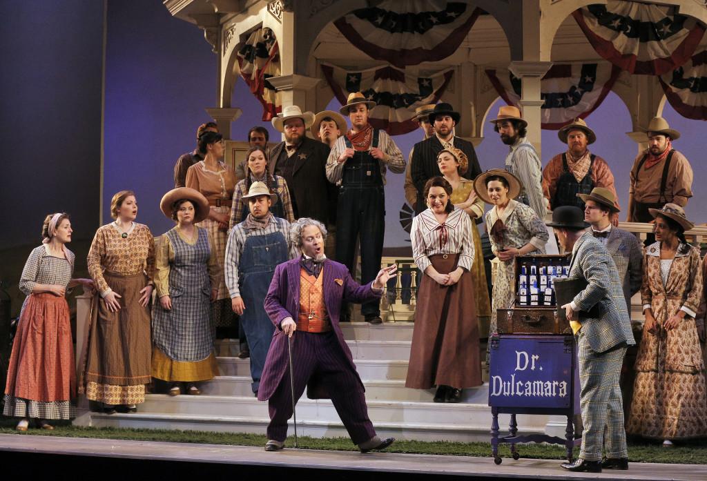 Dulcamara (Patrick Carfizzi) sells his wares, as the Chorus looks on.